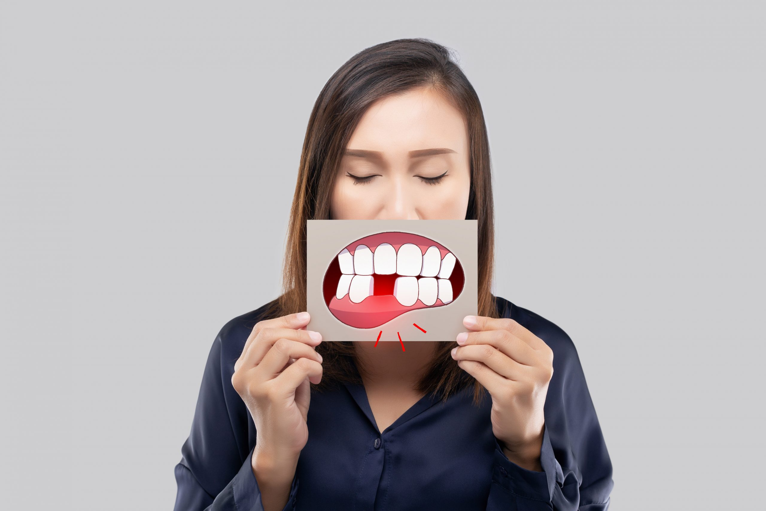 Asian woman in the dark blue shirt holding a brown paper with the broken tooth cartoon picture of his mouth against the gray background, Decayed tooth, The concept with healthcare gums and teeth